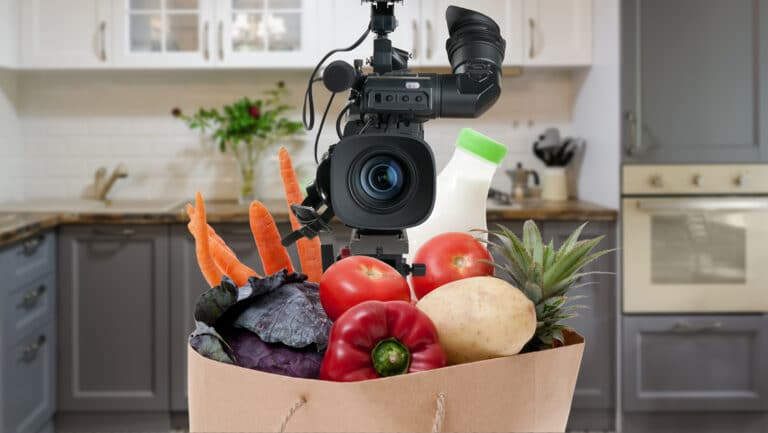 Photo illustration of a video camera inside a grocery bag filled with vegetables in a kitchen. This was used in a blog Current360 created about the importance of fresh video content for marketers.